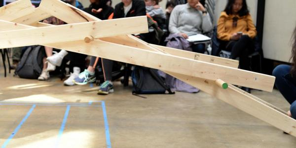 Wooden bridge structure; students in background.