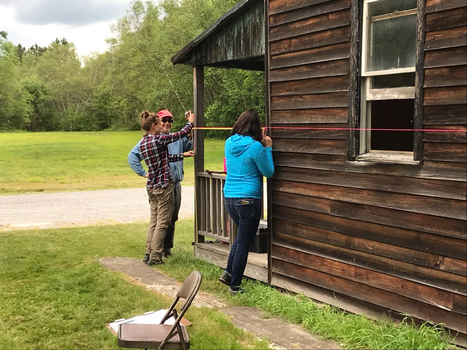 Historic preservation students measuring a wooden house.