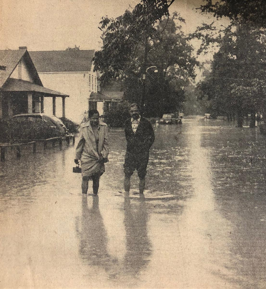 Print magazine image of a couple walking through flooded streets of North Brentwood, Md. in 1955.